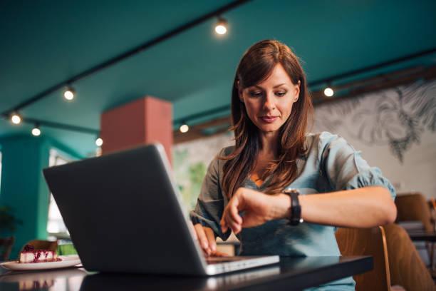 Retrato de una mujer revisando el tiempo en el reloj de pulsera en el café. - foto de stock