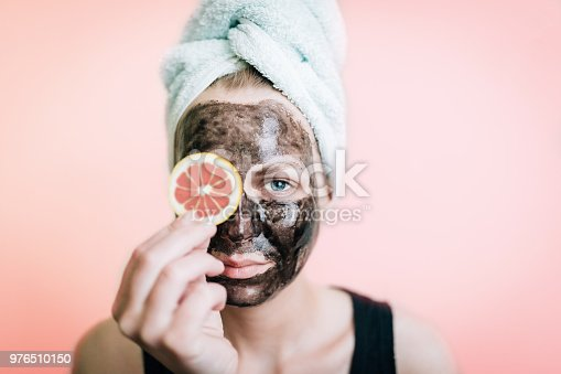 Portrait of a woman cleaning her face with a black mask and citrus fruits