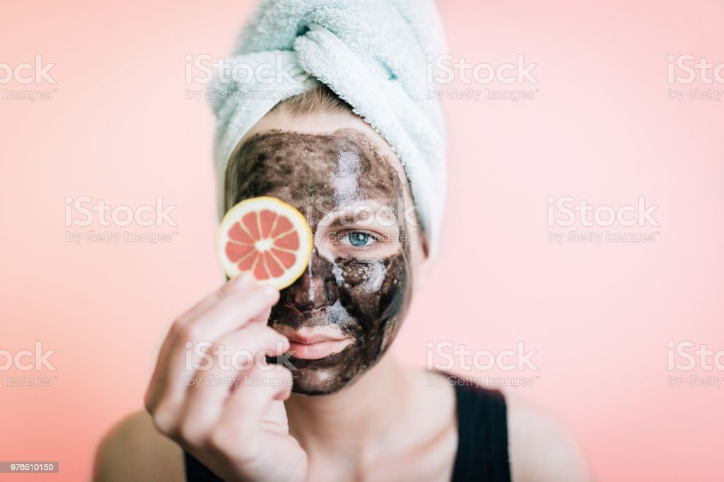 Portrait of a woman cleaning her face with a black mask and citrus fruits stock photo