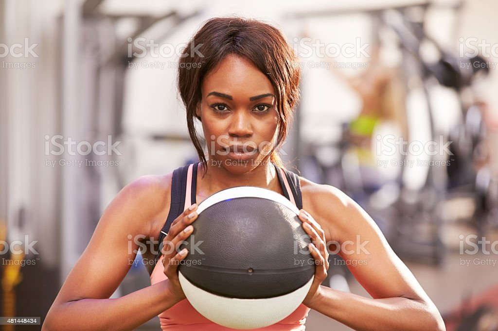 Portrait of a woman holding a medicine ball at gym stock photo