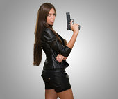 Portrait Of A Woman Holding Gun against a grey background