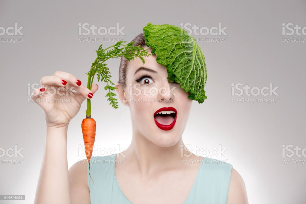Portrait of a woman illustrating a vegan concept holding a carrots and with a cabbage on the head – Foto