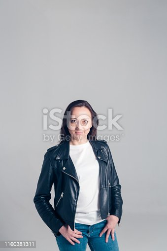 Studio portrait of an attractive young woman in a white t-shirt and black leather jacket against a plain background