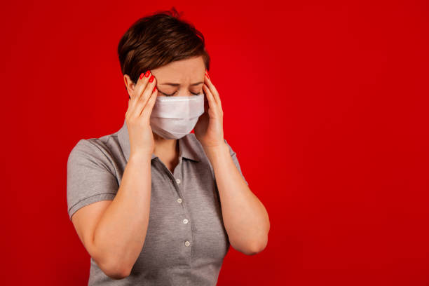 Portrait of a woman in a mask with a symptom of a virus disease. stock photo