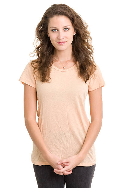 Portrait of a woman in a peach colored shirt and black jeans stock photo