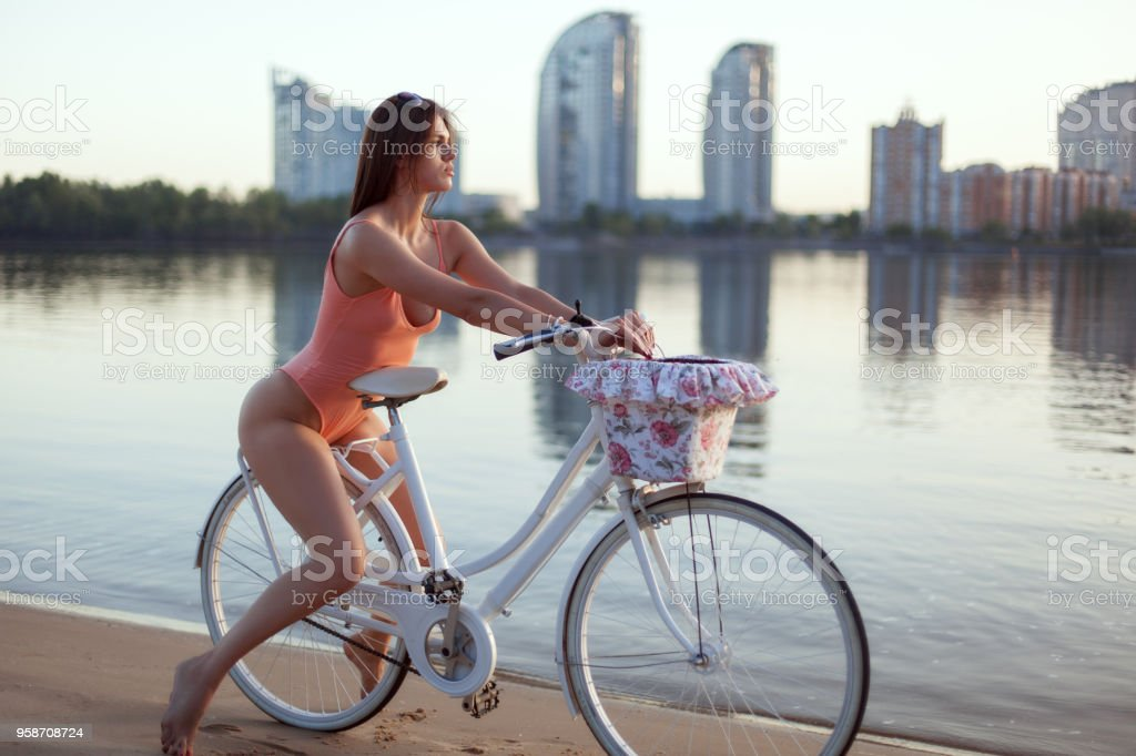 Portrait of a woman in a swimsuit on a bicycle on the river bank. stock photo