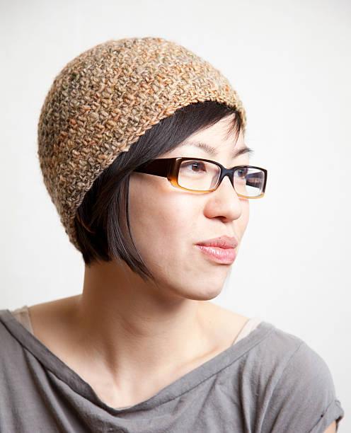 porträt einer frau in brille - zipfelmütze häkeln stock-fotos und bilder