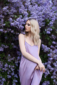 istock Portrait of a woman in lilac bushes in a purple dress. Face of a girl in lilac flowers close up 1264971550