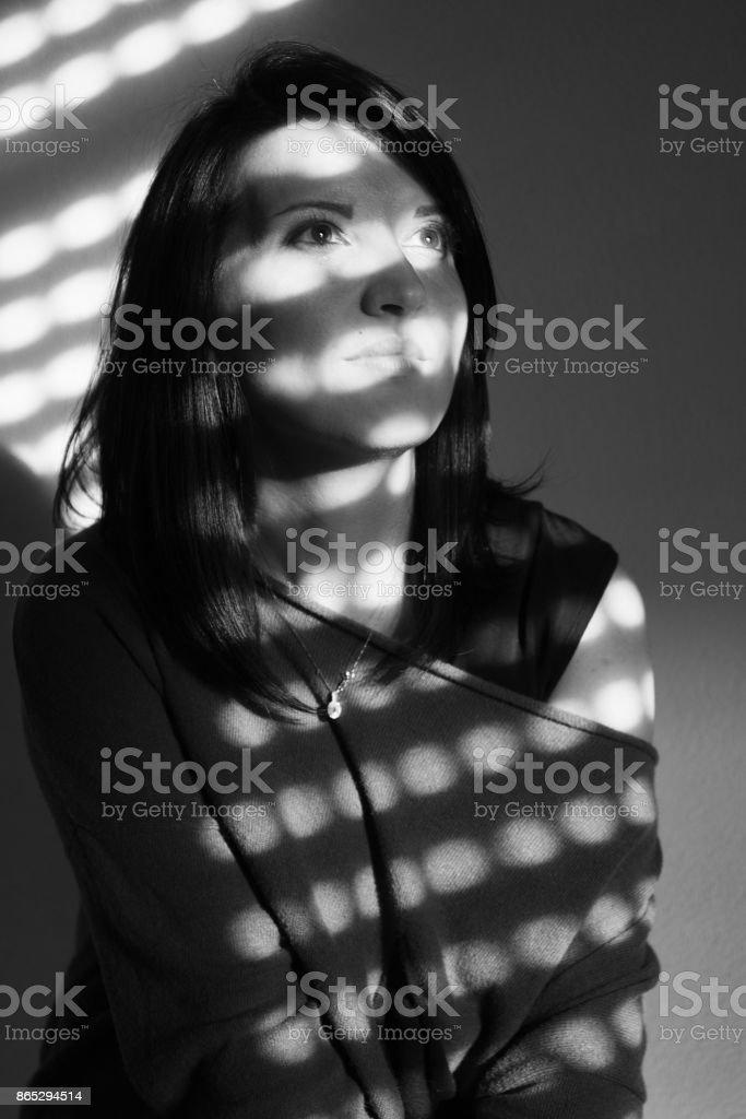Portrait of a woman in sun-dappled light stock photo