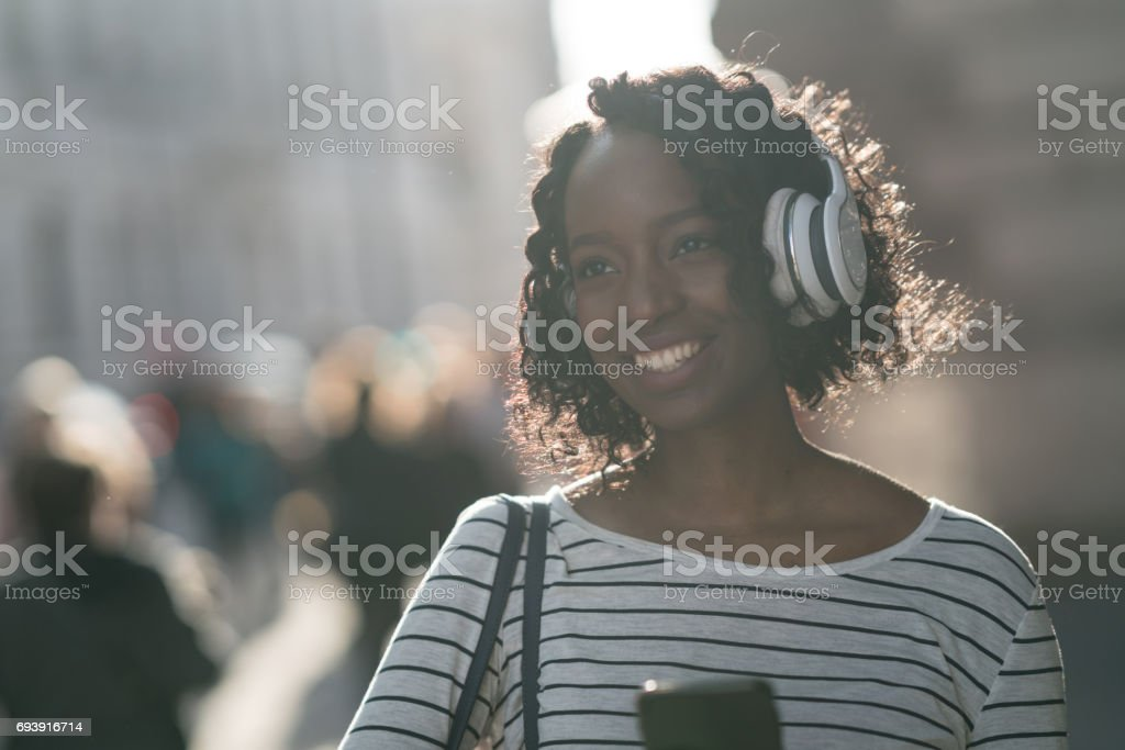 Portrait of a woman listening to music on her phone stock photo
