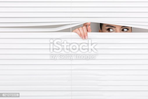 Portrait of a woman looking through out the blinds. Office worker looking through window blinds
