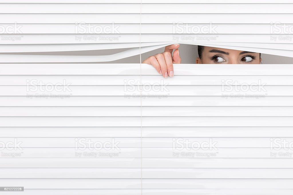 Portrait of a woman looking through out the blinds. - foto de acervo