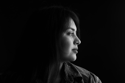 side view of dark portrait of a latin woman on black background, black and white