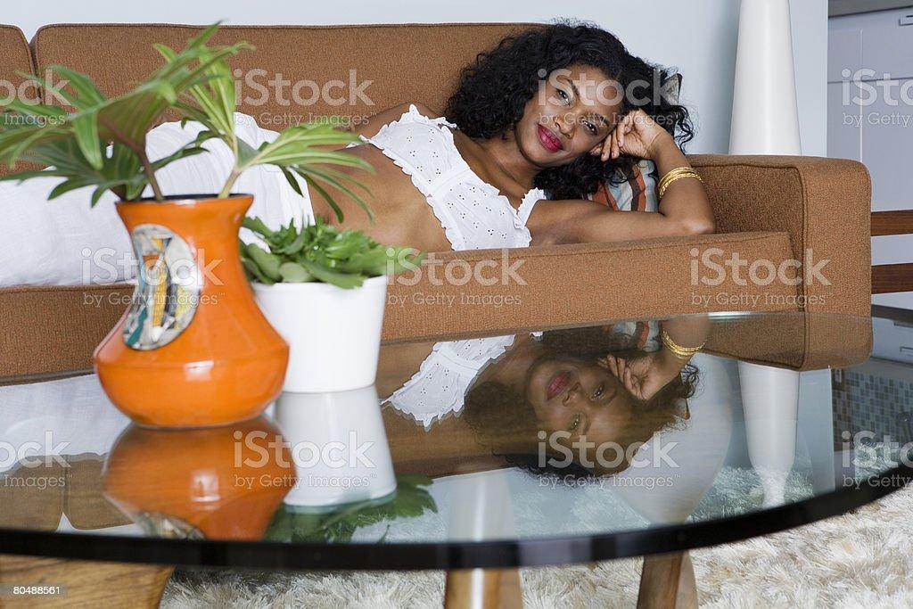 여자 라잉 on 소파와 커피 테이블 근처 royalty-free 스톡 사진