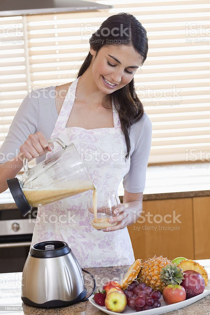 Portrait of a woman pouring frsh juice into the glass royalty-free stock photo