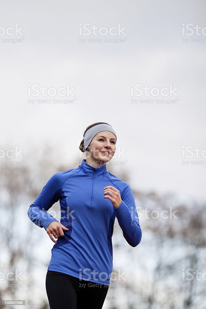 Portrait of a woman running against winter sky royalty-free stock photo