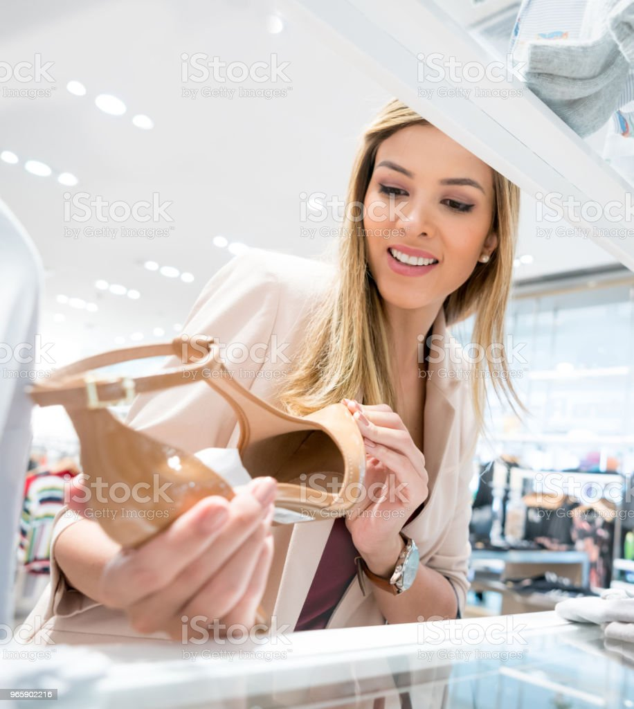 Woman shopping for shoes at a clothing store - Royalty-free 20-29 Years Stock Photo