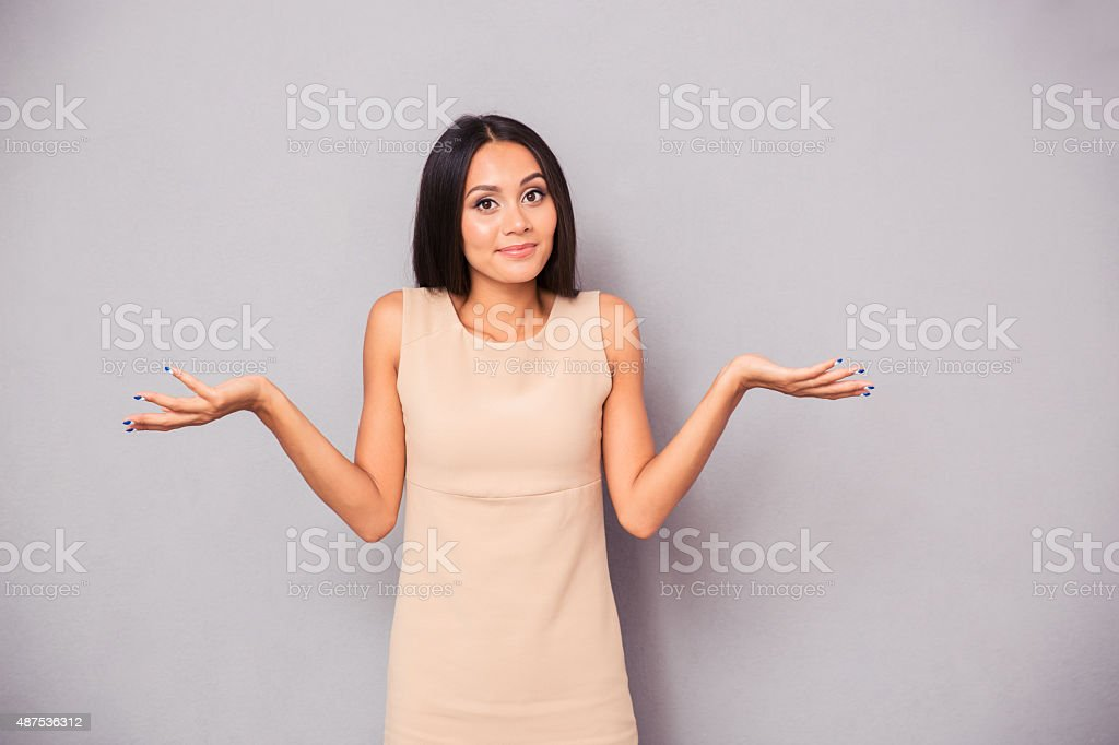 Portrait of a woman shrugging shoulders stock photo