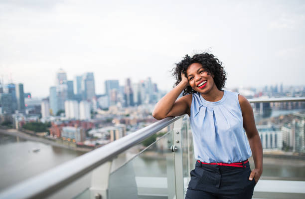 A portrait of a woman standing on a terrace in London. Copy space. A portrait of a laughing black woman standing on a terrace in London. Copy space. blouse stock pictures, royalty-free photos & images