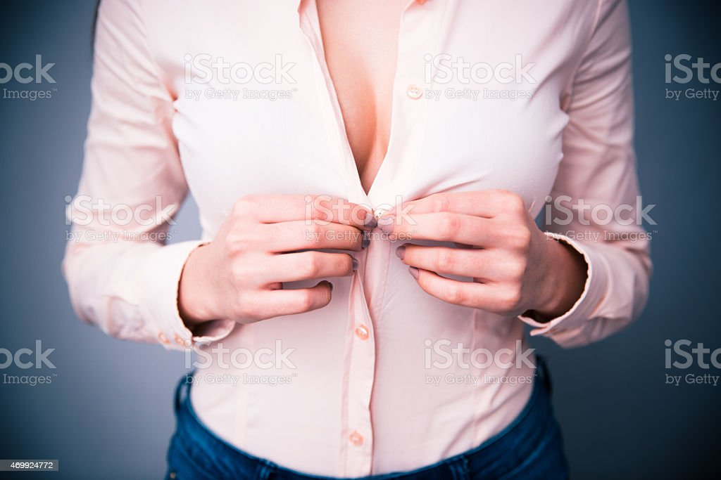 Portrait of a woman unbuttoning her shirt stock photo