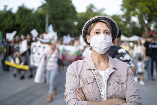Portrait of a woman wearing a face mask in front of a crowd of people demonstrating for their rights