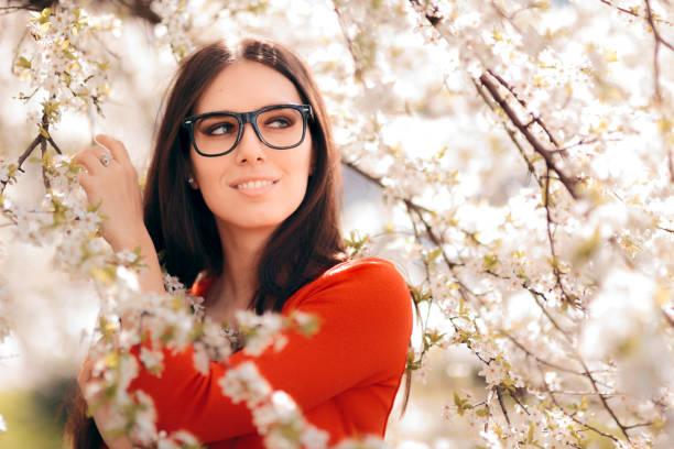 Porträt einer Frau, die eine Augenbrille unter blödem Baum trägt – Foto