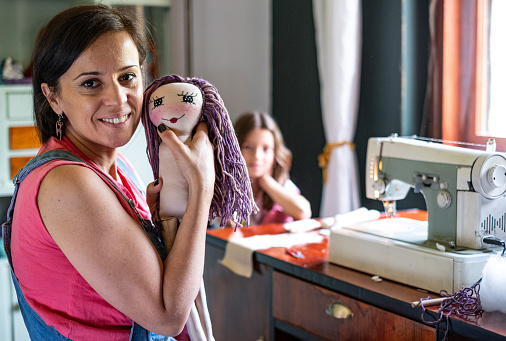 Portrait of a woman whit homemade toy doll