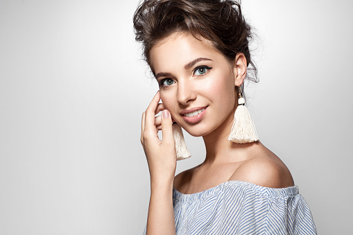Portrait of a  woman with a charming smile in a summer dress and earrings tassels