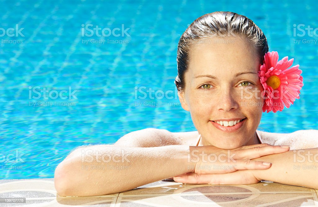 Portrait of a woman with a flower in her hair at the pool royalty-free stock photo