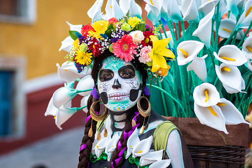 Guanajuato, Mexico - January 12, 2019: Portrait of a woman with beautiful Day of the Dead themed costumes and skull makeup on the streets of Guanajuato, Mexico.