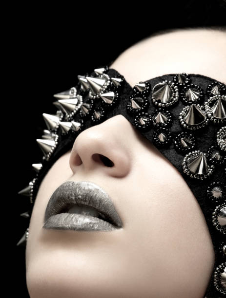 portrait of a woman with fashion spike studs mask and silver lipstick. - punk music stock photos and pictures