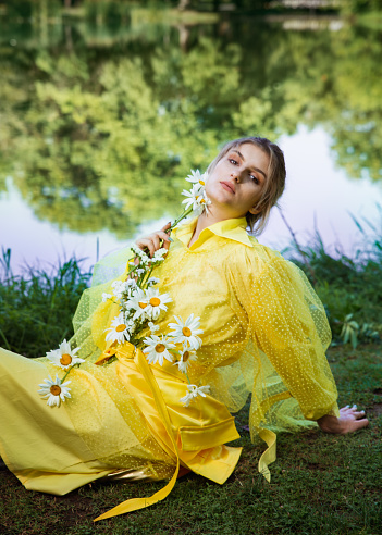Portrait of a beautiful woman with flowers and elegant outfit in the park.