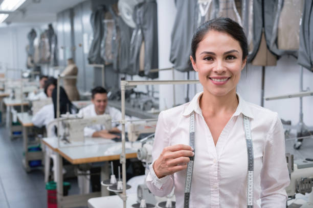 Portrait of a woman working at a clothing factory Portrait of a woman working at a clothing factory as a fashion designer and looking at the camera smiling designer baby stock pictures, royalty-free photos & images