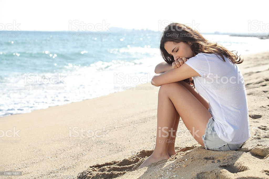 Portrait of a worried girl sitting on the beach stock photo