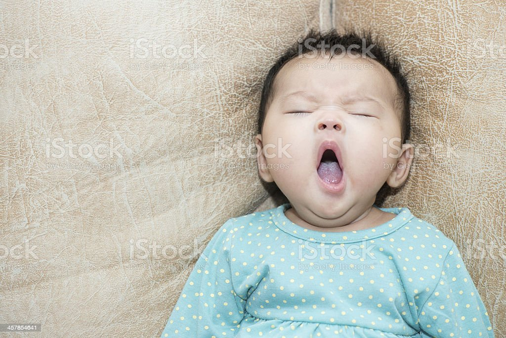 Portrait of a yawning baby girl on leather background stock photo