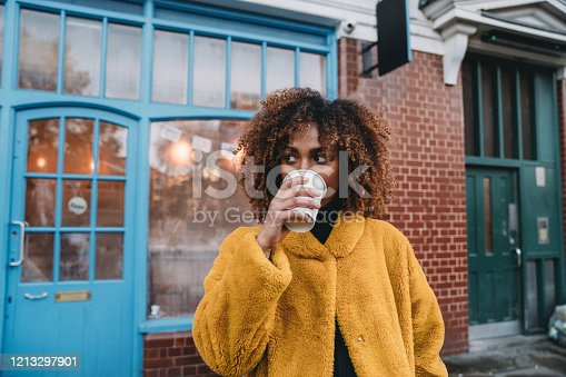 Portrait of a young adult beautiful woman drinking coffee. She's looking away. Mixed race and afro hair.