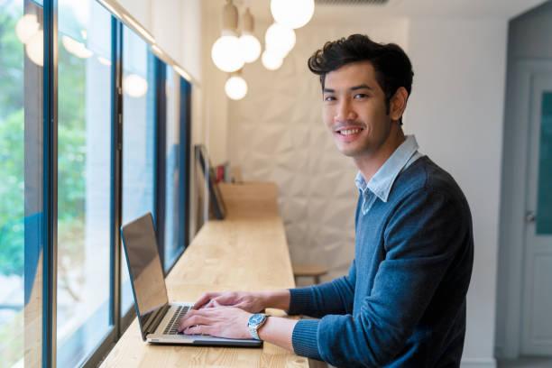 Retrato de um homem adulto jovem sentou-se usando seu laptop em um escritório moderno - foto de acervo