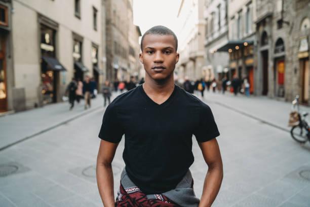 retrato de um homem adulto novo na cidade - camiseta preta - fotografias e filmes do acervo