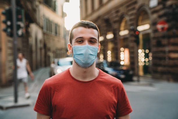 Portrait of a young adult man wearing a protective face mask and looking at camera stock photo