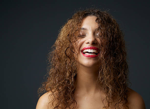 Portrait of a young african american woman laughing Close up portrait of a young african american woman laughing wet hair stock pictures, royalty-free photos & images