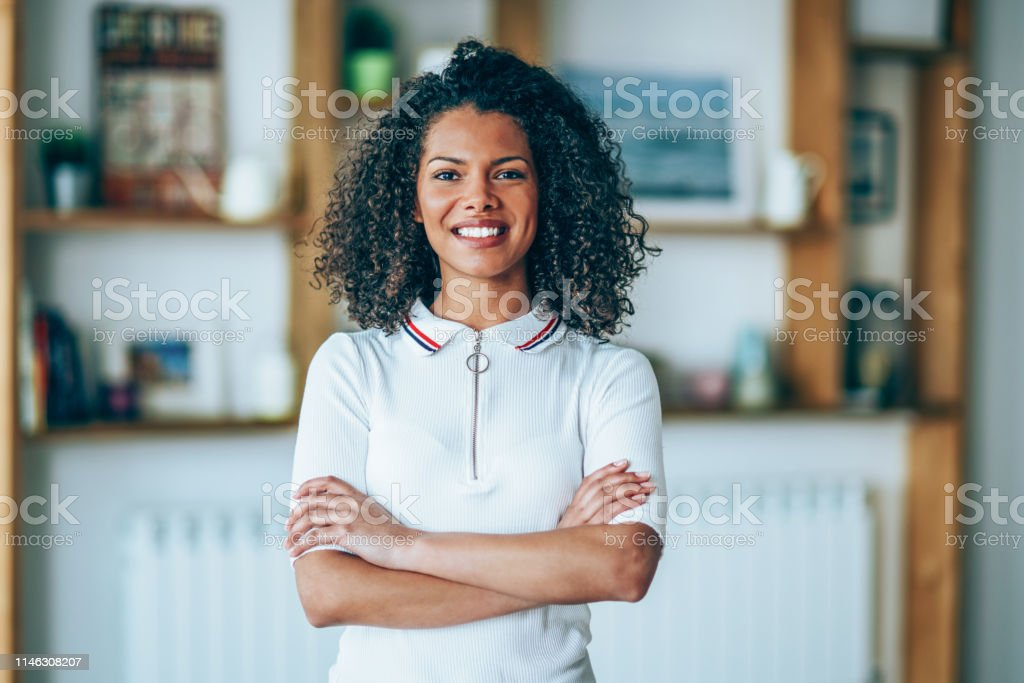 Young African-american ethnicity woman standing with arms crossed and...