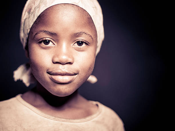 Portrait of a Young African Girl (Isolated on Dark Background) stock photo