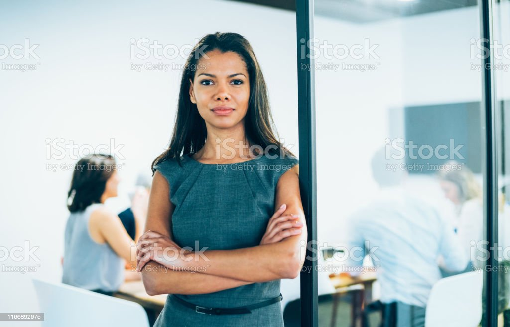 Businesswoman with arms crossed standing in front of her team and...