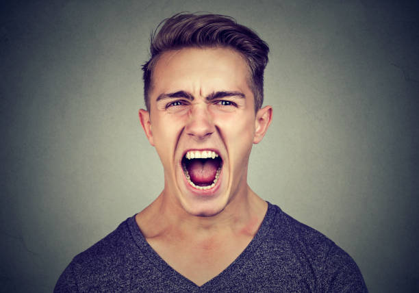 portrait of a young angry man screaming stock photo