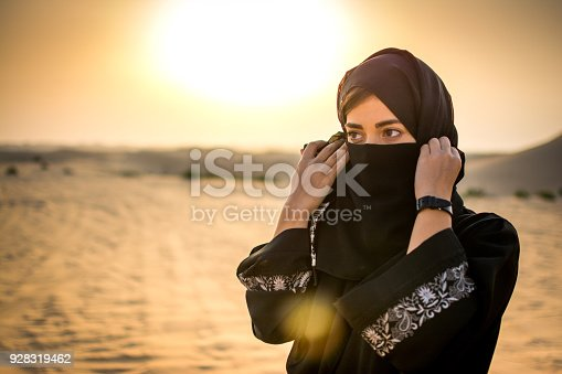 Portrait of a young Arab woman wearing traditional black clothing in the desert during sunset.