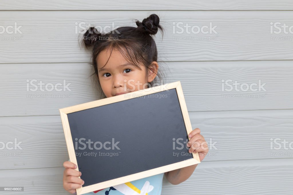 Portrait of a young Asian little girl holding a blank sign blackboard on wood gray background stock photo