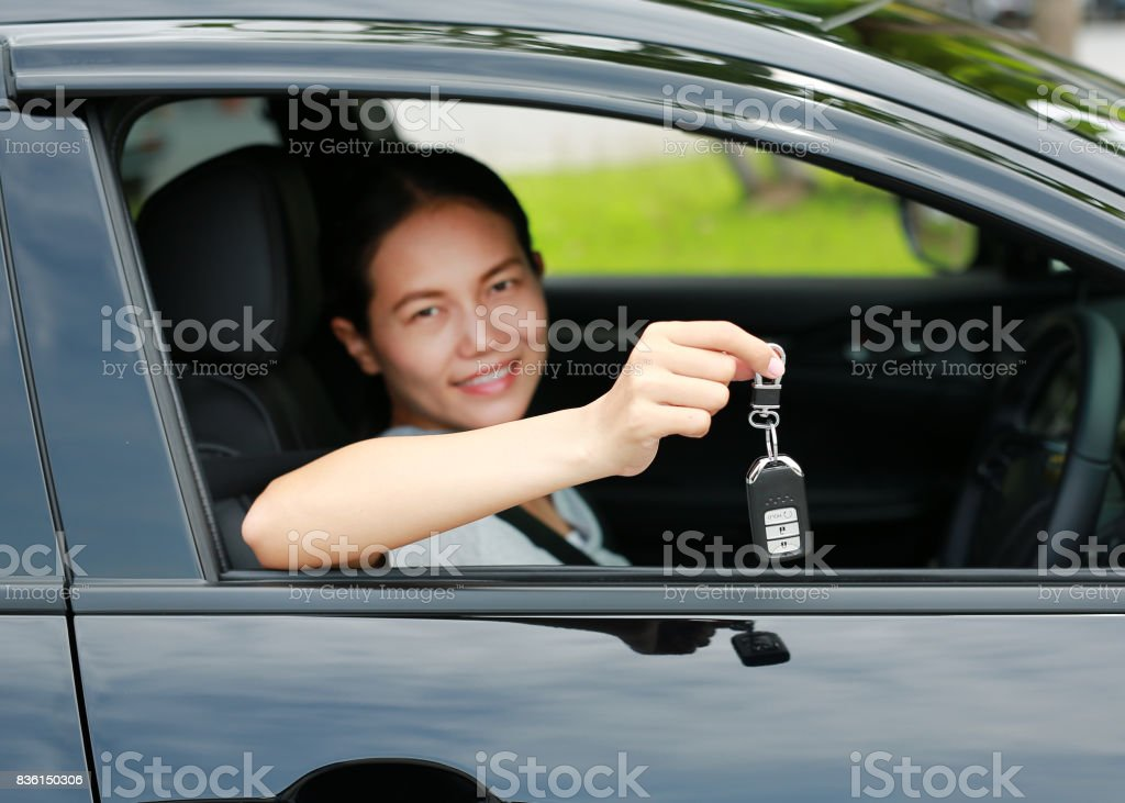 Portrait of a young asian woman inside a car, hold the key out from the window. Focus at a key hanging at her hand. stock photo