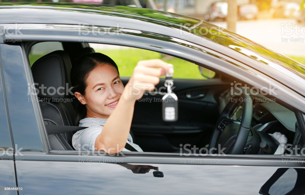 Portrait of a young asian woman inside a car, hold the key out from the window. Focus at her face. stock photo