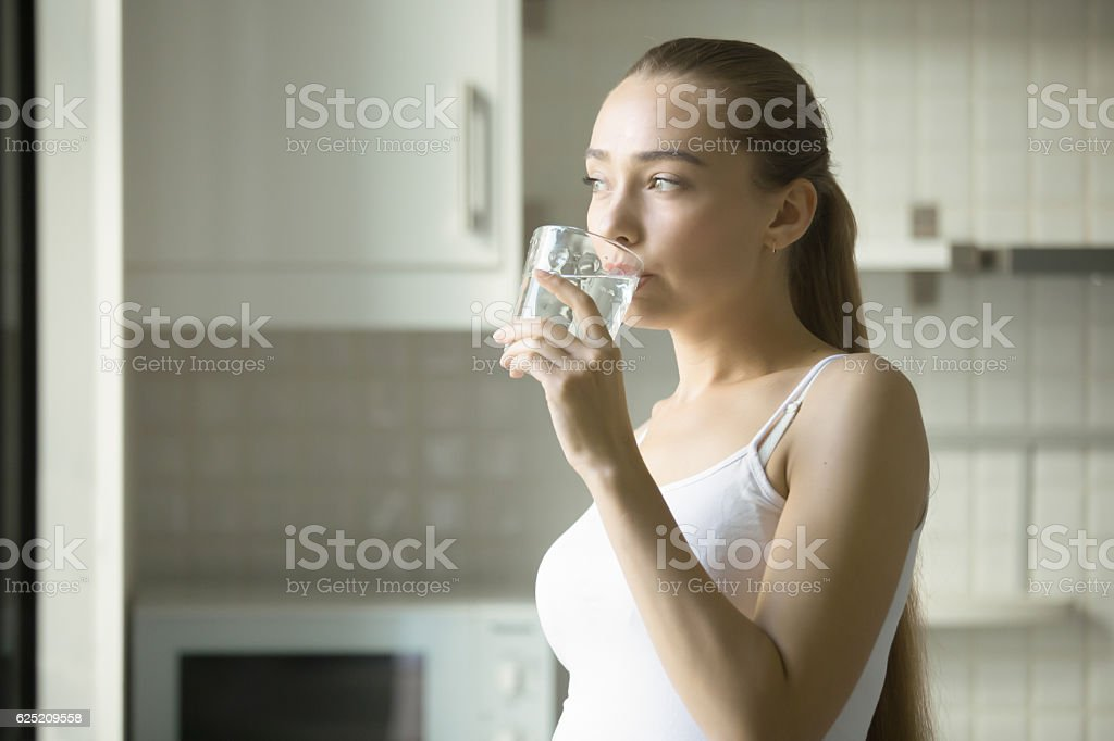 Portrait of a young attractive girl drinking water stock photo