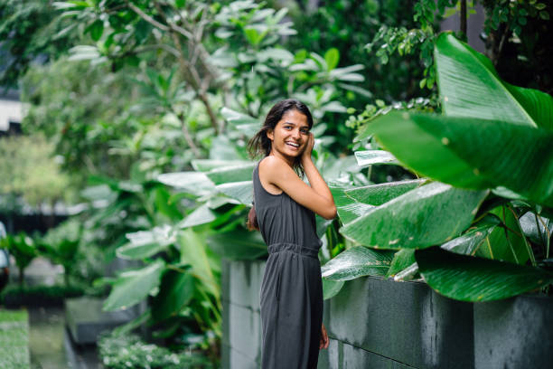 Portrait of a young, attractive Indian woman standing amidst plants in a park during the day. She is standing next to some lush, green plants and is dressed professionally in a simple grey smock. She is laughing candidly as she looks at the camera. amidst stock pictures, royalty-free photos & images